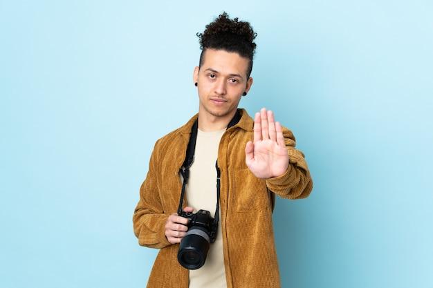 Fotograf mann über isoliertem blau, das stoppgeste mit ihrer hand macht