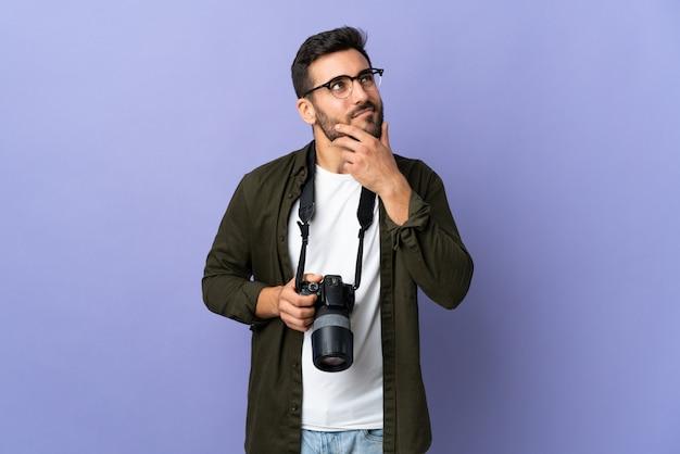 Fotograf mann über lila wand mit zweifeln