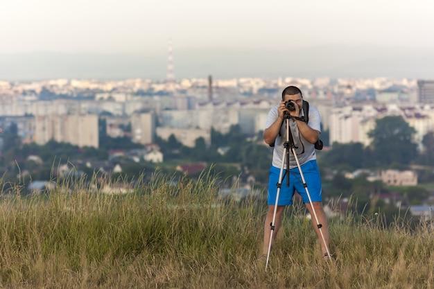 Fotograf mit einer kamera auf einem stativ, das bild macht