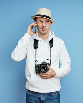 Fotograf mit einer kamera, die am telefon spricht