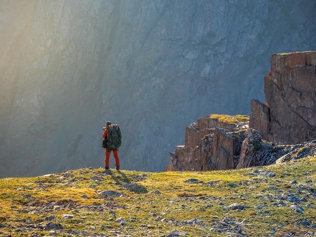 Fotograf mit großem rucksack fotografiert eine wunderschöne berglandschaft am rand einer klippe. gefährliche berge und abgründe im sonnenuntergang.