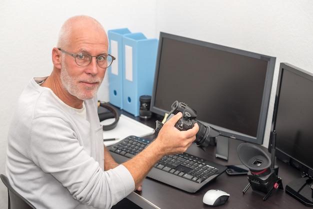 Fotograf mit kamera im büro mit computer