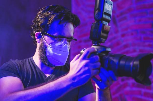 Fotograf mit kn95-maske und professioneller kamera hinter den kulissen der videoproduktion das coronavirus-schutzkonzept