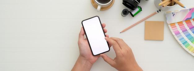 Fotograf mit modell-smartphone auf weißem arbeitstisch mit kamera und anderem zubehör