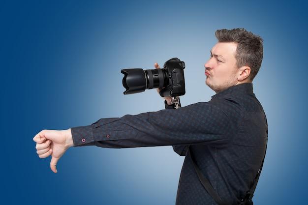 Fotograf mit professioneller digitalkamera zeigt daumen nach unten