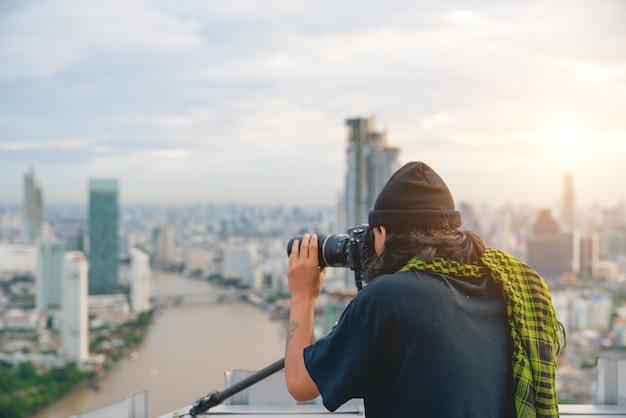 Fotograf mit stativ. junger mann, der foto mit seiner kamera in der stadt macht