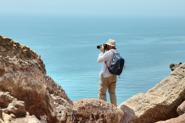 Fotograf reisender in panama auf seinem kopf und rucksack hinter seinen schultern steht am rand einer klippe über dem meer, hormuz, hormozgan, iran.