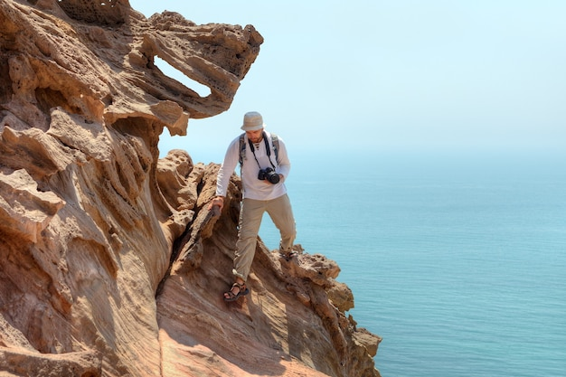 Fotograf reisender klettert klippe über meer, hormuz island, hormozgan, iran.