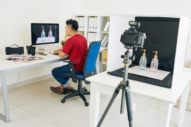 Fotograf retuschiert fotos auf dem computer