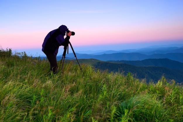 Fotograf silhouette gegen die aufgehende sonne in den bergen
