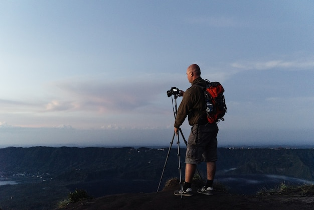 Fotograf tourist montiert seine kamera auf einem stativ für landschaftsfotografie