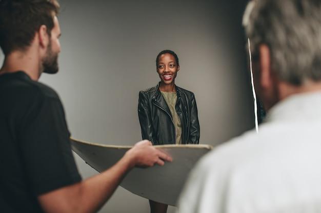 Fotografassistent, der einen reflektor hält