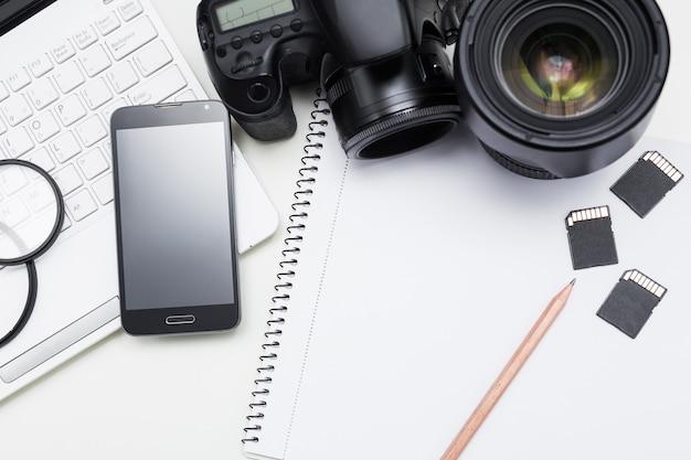 Fotografen arbeitsplatz kamera fotografie ausrüstung laptop smartphone und notizblock mit stift