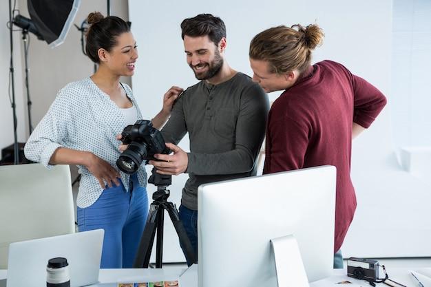Fotografen und models, die aufgenommene fotos mit seiner digitalkamera überprüfen