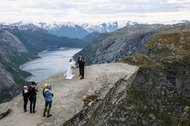 Fotografen und videografen, die eine hochzeitszeremonie außerhalb des geländes auf einem felsfragment in norwegen filmen, das die zunge des trolls genannt wird