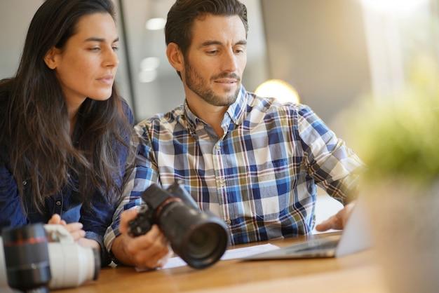 Fotografenkollegen, die fotos auf kamera durchlaufen