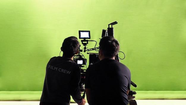 Fotografenteam und filmteam sowie hochauflösende online-videokamera und grüner chroma-key für filmaufnahmen im großen studio.