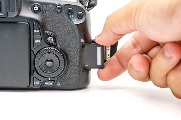 Fotografhand, die moderne kamera dslr der karte sd-codierten karte hält
