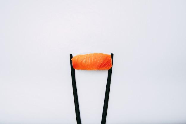 Fotografie des japanischen lachs-nigiri mit schwarzen stäbchen