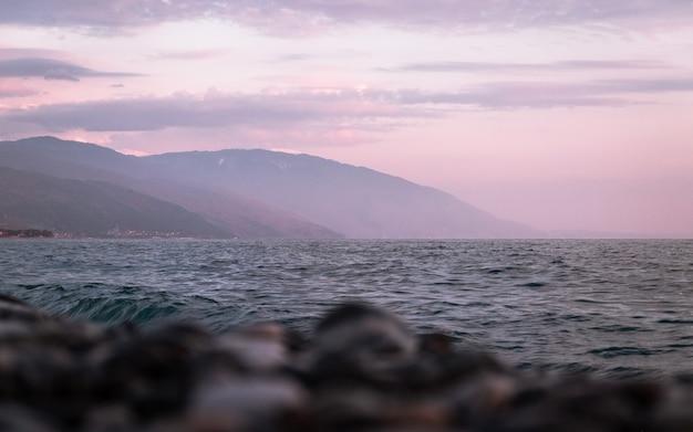 Fotografie des meeres und der berge im hintergrund