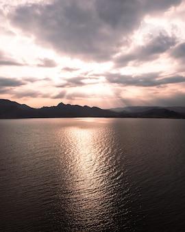 Fotografie des sonnenuntergangs auf dem see. orangefarbene reflexion