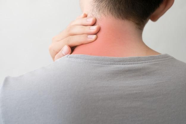 Fotografie eines mannes von hinten mit schmerzen und nackenverletzung