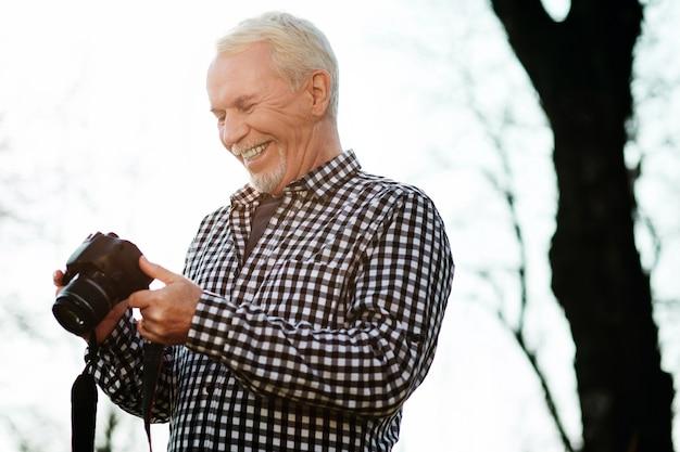Fotografie im park. niedriger winkel des begeisterten älteren mannes, der lacht und kamera benutzt
