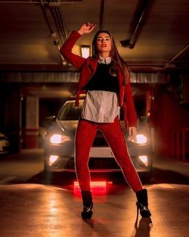 Fotografie mit rotem neon vor einem auto auf einem parkplatz. porträt einer hübschen jungen blonden kaukasischen frau