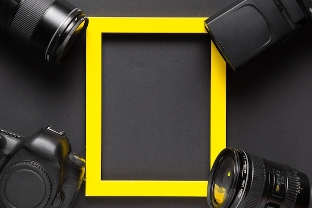 Fotografiekonzept mit kamera und gelbem rahmen mit kopieraum