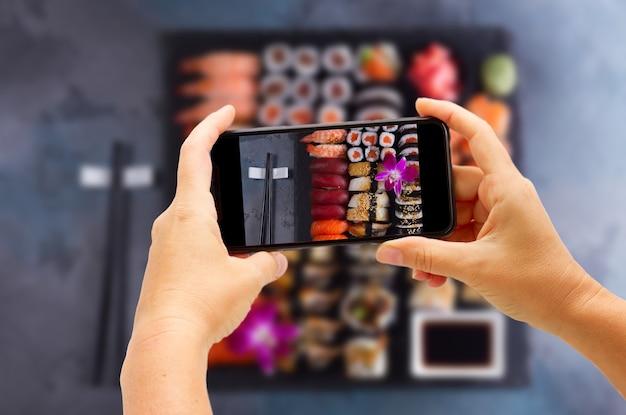 Fotografieren eines großen japanischen sushi-sets mit schwarzen essstäbchen aus holz auf grau