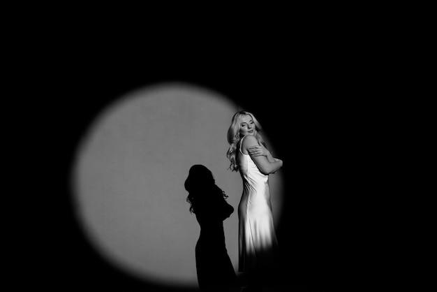Fotografieren mit projektoren, schwarz und weiß, hell und dunkel, mit der figur eines schönen mädchens posiert, modische muskelaufbau.