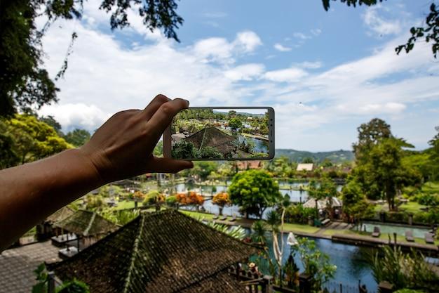 Fotografieren mit smartphone in der hand. reisekonzept. wasserpalast von tirta gangga in bali.