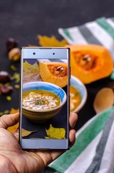 Fotografieren mit smartphone von der kürbiscremesuppe