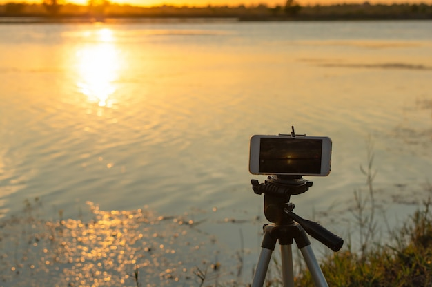 Fotografieren sie den sonnenuntergang am fluss mit einem mobilen smartphone auf einem stativ