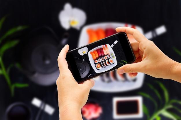Fotografieren von japanischem sushi mit teekanne und teetassen auf schwarzem holzhintergrund, ansicht von oben
