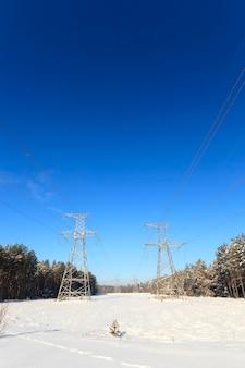 Fotografierte elektrische strommasten aus der nähe, die sich im feld befinden