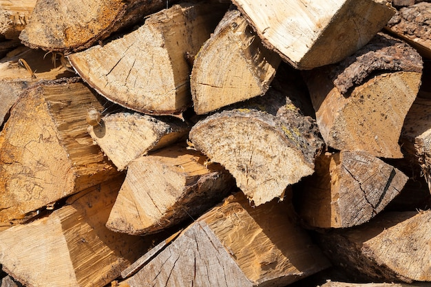Fotografierte nahaufnahme eines gelben stammes eines in brennholz gehackten schnittholzes. holz wird parallel zu den vorherigen reihen gestapelt. foto des dorflebens