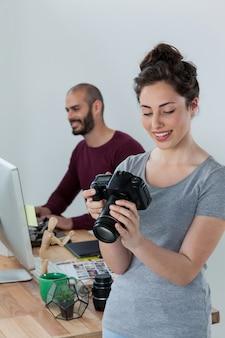 Fotografin, die aufgenommene fotos in ihrer digitalkamera überprüft