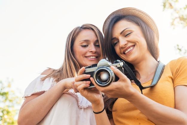 Fotografin, die ihrer freundin ein bild zeigt. freunde-konzept.