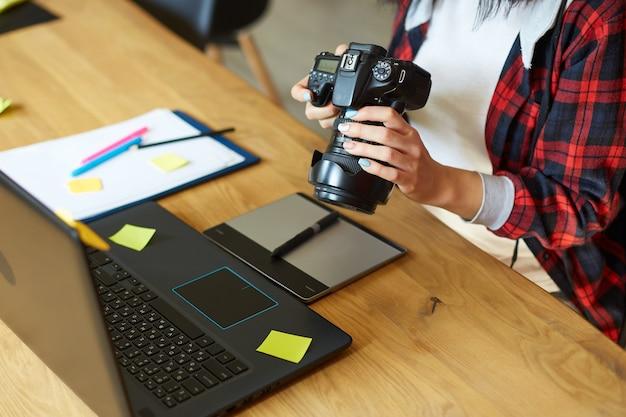 Fotografin, die in einem kreativen büro arbeitet und kamera hält, am schreibtisch und foto auf laptop retuschiert, retuschierarbeitsplatz im fotostudio, erfolgreiches freiberufliches künstlergeschäft, fotografiekonzept