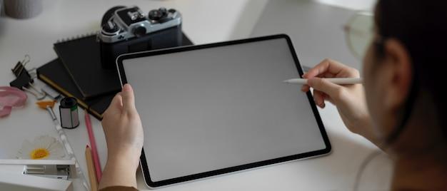 Fotografin, die mit mock-up-tablett auf tisch mit kamera und zubehör im studio arbeitet