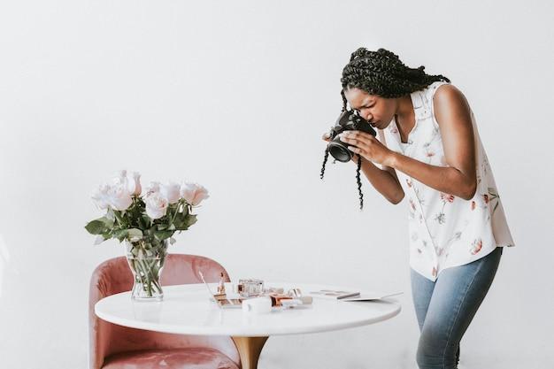 Fotografin fotografiert schönheitsprodukte auf dem tisch