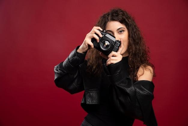 Fotografin in allen schwarzen outfits, die bilder mit einer kamera machen.