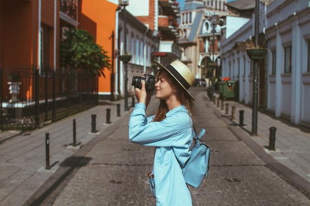 Fotografreisender im hut und mit rucksack macht fotos des anblicks beim gehen entlang die straße einer europäischen stadt. lebensstil auf reisen