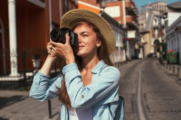Fotografreisender macht fotos von sehenswürdigkeiten beim gehen entlang der straße einer europäischen stadt. urlaub und ferienreisen