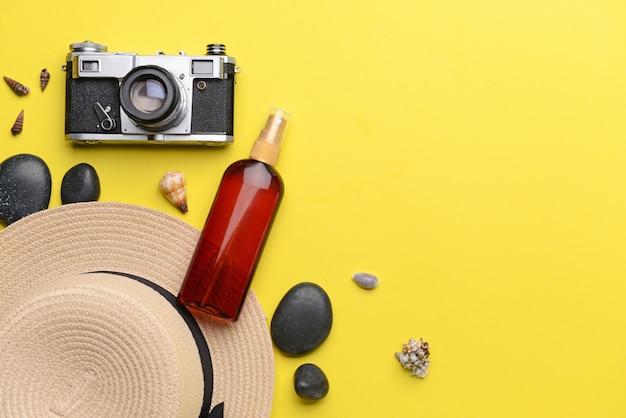 Fotokamera mit hut und sonnenschutzöl auf gelb