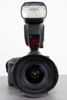 Fotokamerablitz mit kamera auf grau
