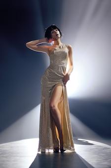 Fotomodell in langem kleid mit tiefem schnitt auf der bühne unter hauptbeleuchtung