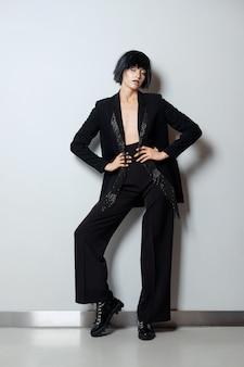 Fotomodell in schwarzer perücke, hosenanzug mit perlenfransen und groben spitzen mit schnürung