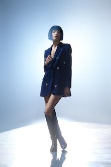 Fotomodell mit bob-frisur in blauer jacke mit edelsteindekor und in weiten hohen stiefeln auf der bühne unter hauptbeleuchtung